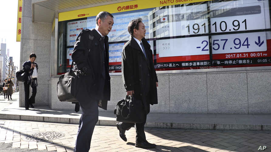 Men walk past an electronic stock indicator of a securities firm in Tokyo, Jan. 31, 2017.