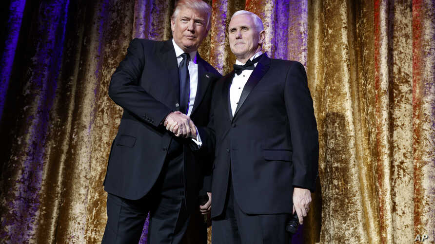 President-elect Donald Trump, left, stands with Vice President-elect Mike Pence during the presidential inaugural Chairman's Global Dinner in Washington, Jan. 17, 2017.