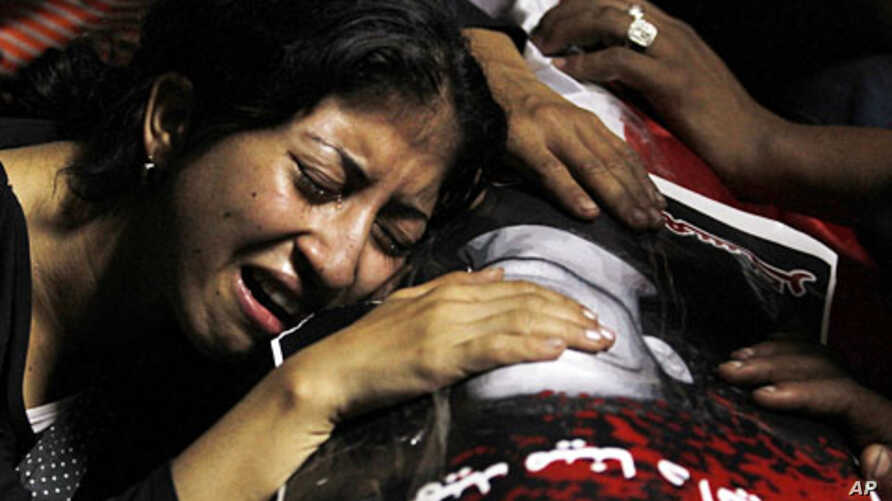 An Egyptian Christian woman mourns on the coffin of Coptic Christian Mina Demian, who was killed during clashes with soldiers and riot police late Sunday, at the morgue of the Coptic Hospital in Cairo October 10, 2011.