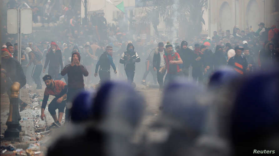 Anti-riot police officers clash with people protesting against President Abdelaziz Bouteflika, in Algiers, Algeria, March 8, 2019.