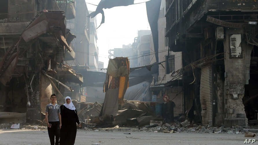 Syrians walk past anti-sniper curtains remaining in a street on May 12, 2014 in a destroyed neighbourhood of the Old City of Homs.