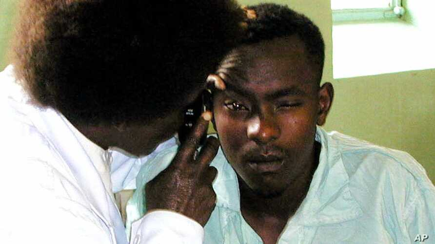 FILE - A nurse examines the eyes of John Kabiru Njenga in Kenyatta National Hospital in Nairobi, where he was admitted after drinking home brewed alcohol.