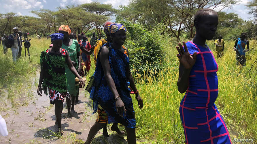 South Sudanese women walk to the site of a U.N. World Food Program (WFP) food aid air drop near the town of Katdalok, in Jonglei State of South Sudan, July 30, 2018.
