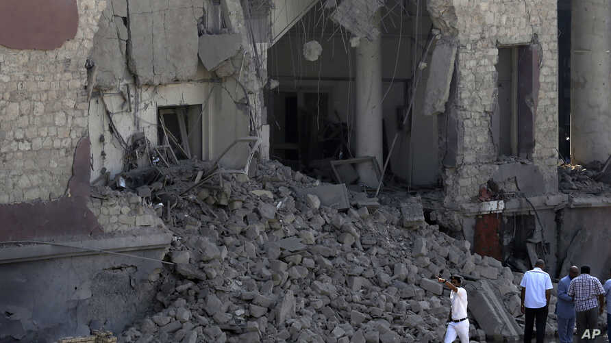 Egyptian policemen stand at the base of the crumbled facade of the Italian consulate following a blast that killed at least one person in Cairo, Egypt, July 11, 2015.