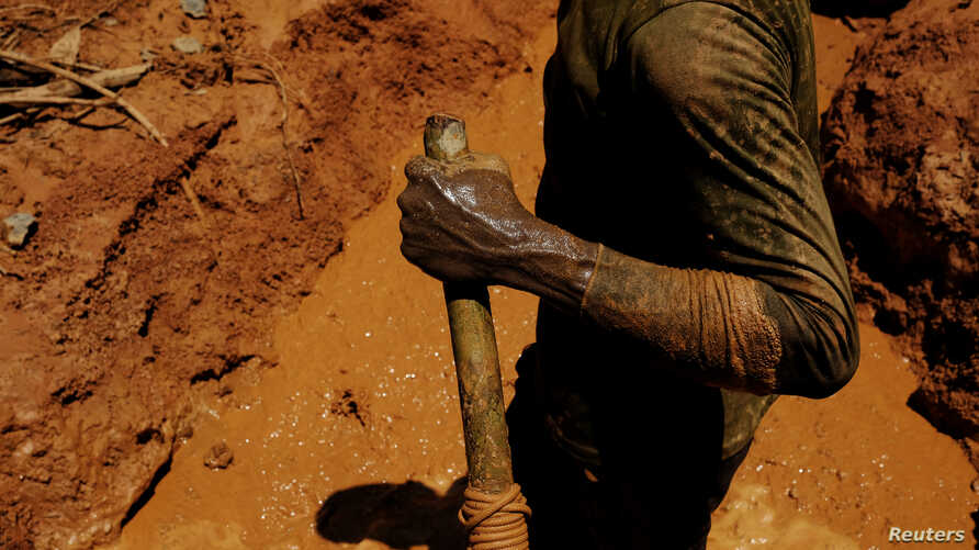 A garimpeiro uses a stick as an accelerator for a diesel engine while working a wildcat mine, also known as garimpo, at a deforested area of Amazon rainforest in Brazil, Aug. 6 2017.