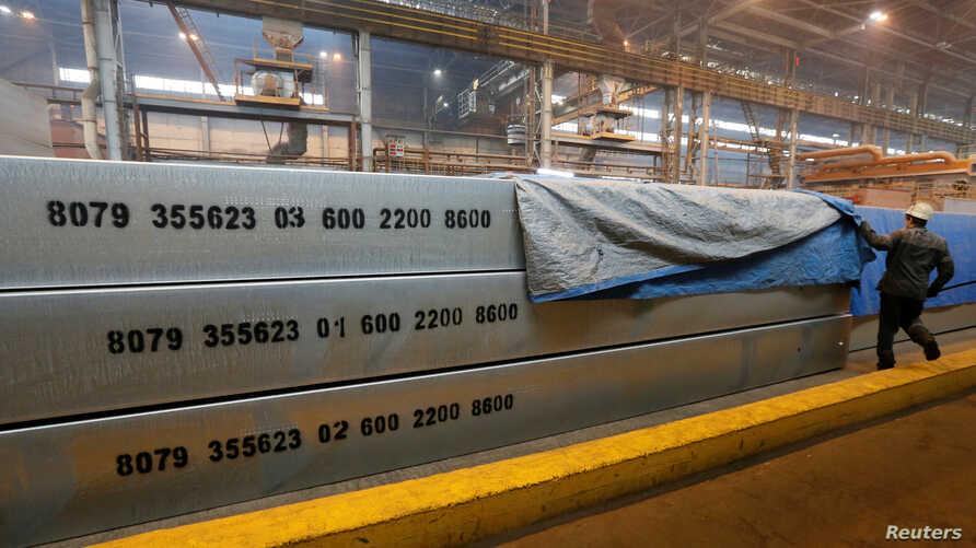 FILE - An employee removes a covering of 13-meter aluminium ingots at the foundry shop of the Rusal Krasnoyarsk aluminium smelter in Krasnoyarsk, Russia, July 27, 2016. Rusal is among Russian companies on a new U.S. sanctions list.