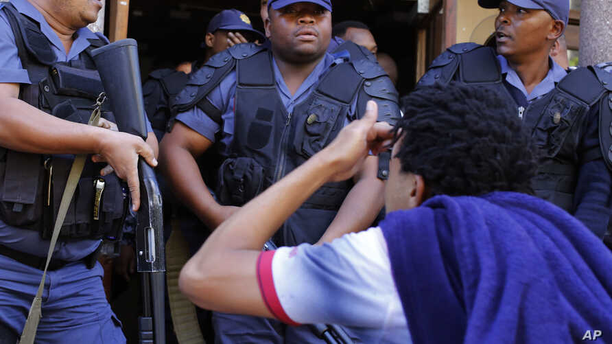 South African police disperse students after they broke a window at the University of Cape Town campus in Cape Town, South Africa, Oct. 17, 2016.