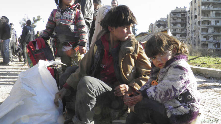 Syrian children sit with their belongings as they wait to be evacuated from a besieged area of Homs Feb. 12, 2014.