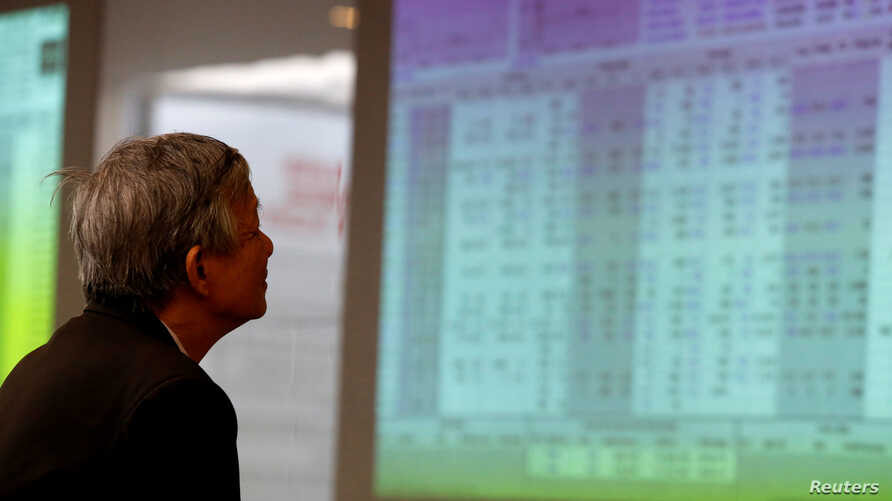 A investor looks at stock market screens at a securities company in Hanoi, Vietnam, April 20, 2016.