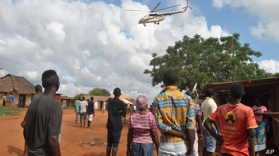 Residents look at a police helicopter patrolling near the closed house, where Italian volunteer for the Italian charity Africa Milele lived before she was seized, in Chakama trading centre of Magarini, Kilifi County, Kenya Nov. 21, 2018.
