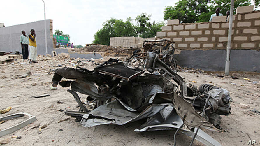 A damaged car is seen along a road after a bomb blast in Maiduguri in the northeastern state of Borno,  June 29, 2011