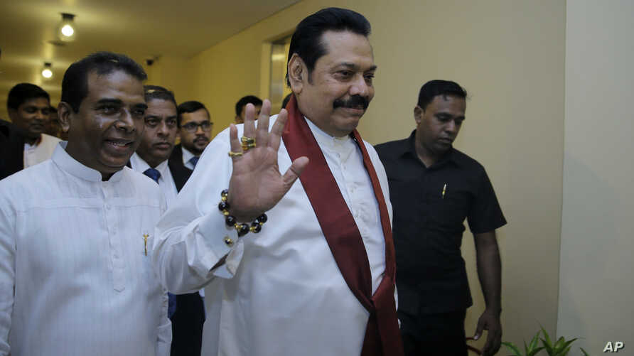 FILE - Sri Lanka's disputed Prime Minister Mahinda Rajapaksa gestures as he arrives for a meeting with his supporting lawmakers at the parliamentary complex in Colombo, Sri Lanka, Nov. 29, 2018.