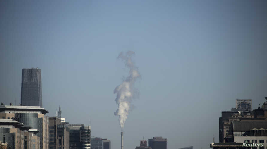 Steam billows from a chimney of a heating plant near the World Trade Centre Tower III, a 330-meter-tall (1,083 feet) skyscraper, in central Beijing, Feb. 4, 2013.