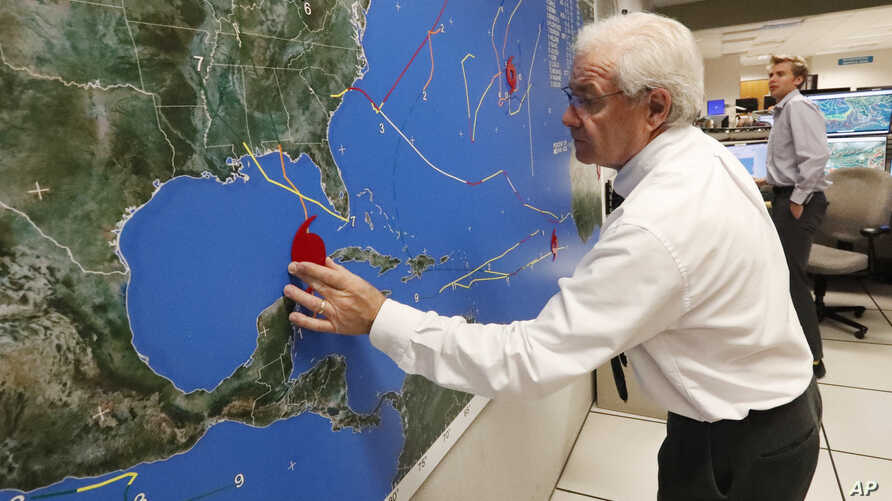 National Oceanic and Atmospheric Administration public affairs officer Dennis Feltgen updates the progress of Hurricane Michael on a large map, Oct. 9, 2018, at the Hurricane Center in Miami.