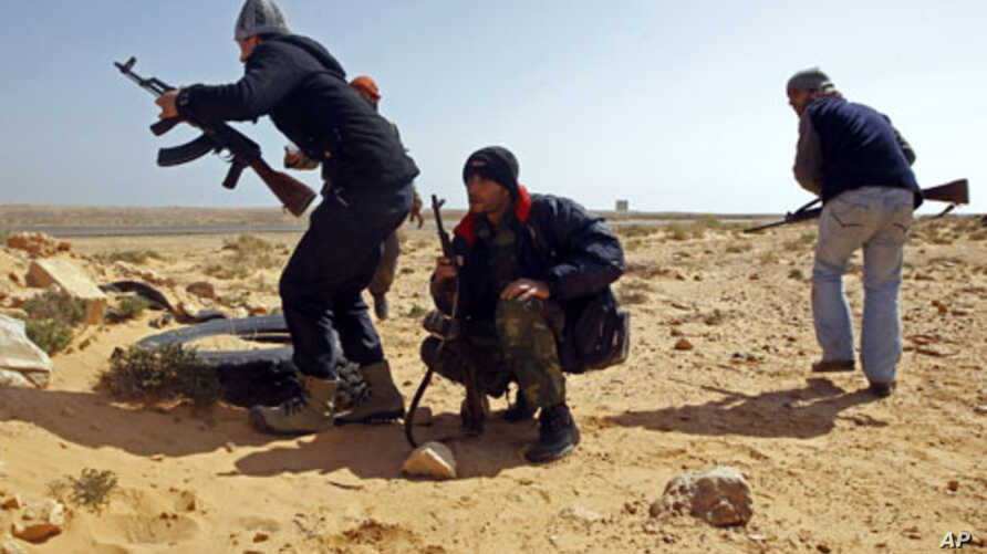 Rebel fighters survey the situation during a battle along the road between Ras Lanuf and Bin Jiwad, Libya, March 10, 2011