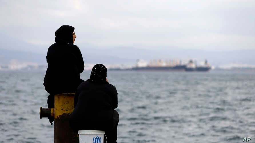Two women sit on a dock of a refugee camp which houses about 3,200 refugees and migrants, in the western Athens' suburb of Skaramagas, Aug. 25, 2016.