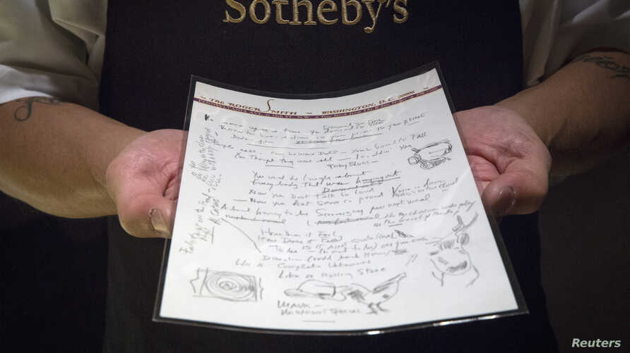 A Sotheby's employee shows the handwritten lyrics for Bob Dylan's 'Like a Rolling Stone' song that is part part of a collection from; 'A Rock and Roll History: Presley to Punk' at Sotheby's auction house in New York, June 20, 2014.