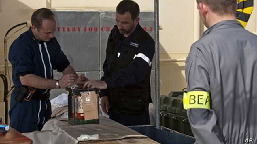 A BEA air accident inquiry official (R), surveys the handling of a flight data recorder aboard ship, May 2, 2011