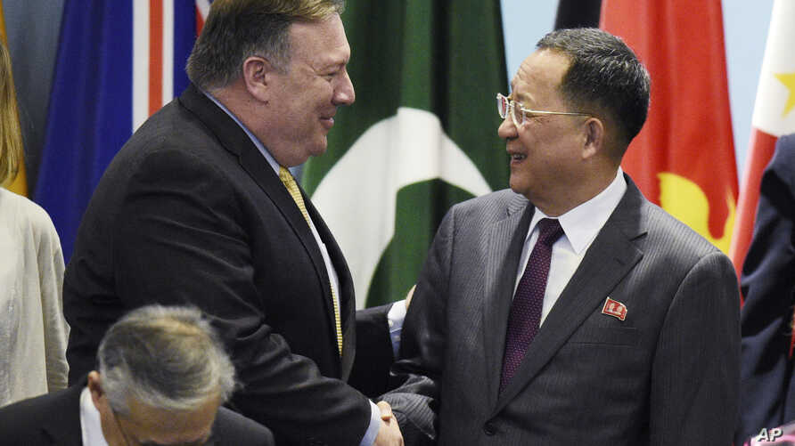 U.S. Secretary of State Mike Pompeo, left, greets North Korea's Foreign Minister Ri Yong-ho as they prepare for a group photo at the 25th ASEAN Regional Forum Retreat in Singapore, Saturday, Aug. 4, 2018.