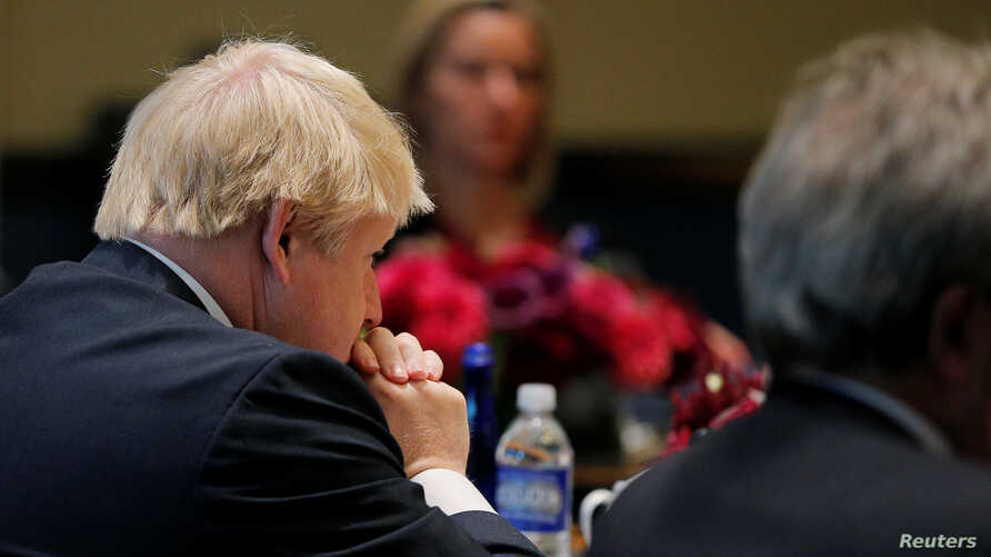 FILE - United Kingdom Foreign Secretary Boris Johnson (L) and European Union High Representative Federica Mogherini (rear) listen as United States Secretary of State John Kerry speaks during a meeting of foreign ministers from Germany, the UK, France