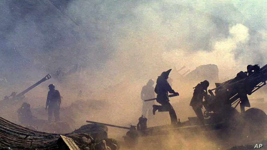 FILE - Indian artillery guns are engulfed in smoke in Dras, some 155 kilometers (96 miles) north of Srinagar, India, as Indian troops fight Pakistani intruders in the disputed Kashmir, July 10, 1999.