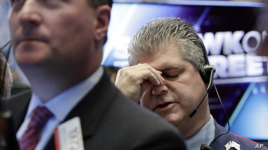 FILE - Trader John Panin, right, works on the floor of the New York Stock Exchange, Oct. 17, 2016. By the end of the week, the Dow Jones Industrial Average had rebounded from a triple-digit loss.