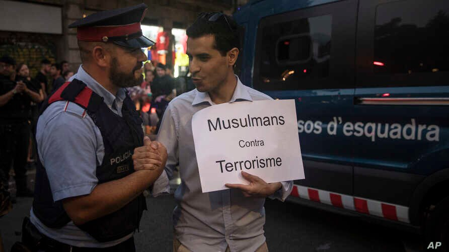 """A Catalan policeman shakes hands with a demonstrator holding a banner that reads: """"Muslims Against Terrorism,"""" during a protest by the Muslim community condemning the attack in Barcelona, Spain, Aug. 21, 2017."""