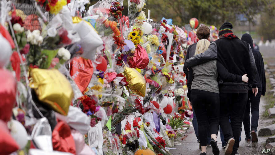People walk arm-in-arm past a memorial outside the school for victims following a deadly shooting nearly a week earlier, in Marysville, Washington, Oct. 30, 2014.