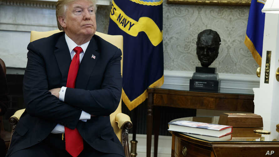 President Donald Trump listens during a meeting with North Korean defectors where he talked with reporters about allowing the release of a secret memo on the FBI's role in the Russia inquiry, in the Oval Office of the White House, Feb. 2, 2018, in Wa