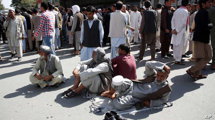 Afghan protesters sit on the ground to block one of the main Kabul streets during a demonstration against the government, in Kabul, Afghanistan, Oct. 7, 2015.
