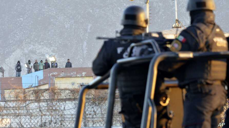 Inmates stand on the rooftop of the Topo Chico prison as police guard the perimeters, after a riot broke out around midnight in Monterrey, Mexico, Feb. 11, 2016.