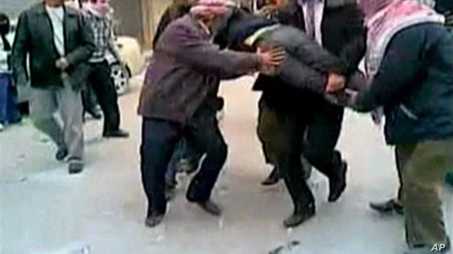 In this still image taken from video protesters in a Damascus suburb purportedly carry a wounded comrade Friday, December 30, 2011. Image content not independently verifiable.