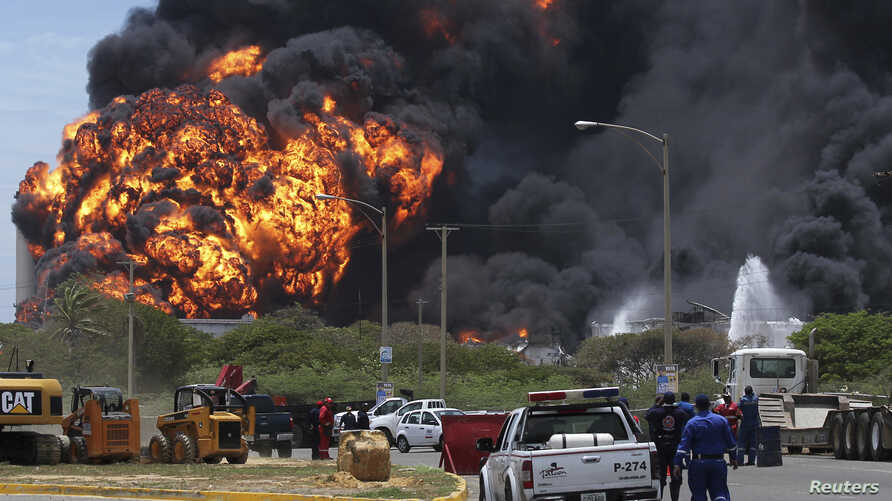A fire burned for a third day in two fuel storage tanks at Venezuela's biggest refinery, August 27, 2012.