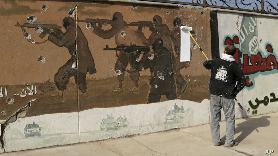 FILE - A volunteer begins to paint over a mural that had been displayed by the Islamic State group, on the eastern side of Mosul, Iraq.