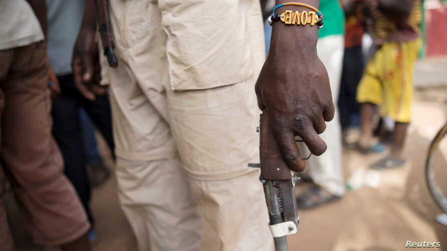 FILE - A member of the of an Anti-Balaka armed militia displays his weapon in the town of of Bocaranga, Central African Republic, April 28, 2017.
