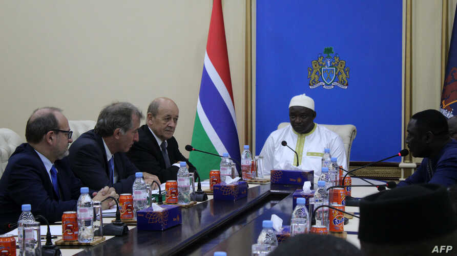 French Foreign Affairs Minister Jean-Yves Le Drian (3L) speaks with Gambia's President Adama Barrow (C) and officials during a meeting at The Presidential Palace in Banjul, Nov. 5, 2018.
