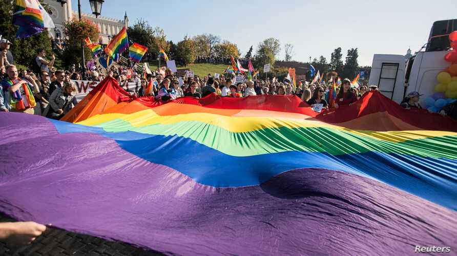 """Participants display a large rainbow flag at the """"Equality Parade"""" rally in support of the LGBT community in Lublin, Poland, Oct. 13, 2018. More than 200 Polish schools had planned to take part in """"Rainbow Friday,"""" an anti-discrimination event set fo"""