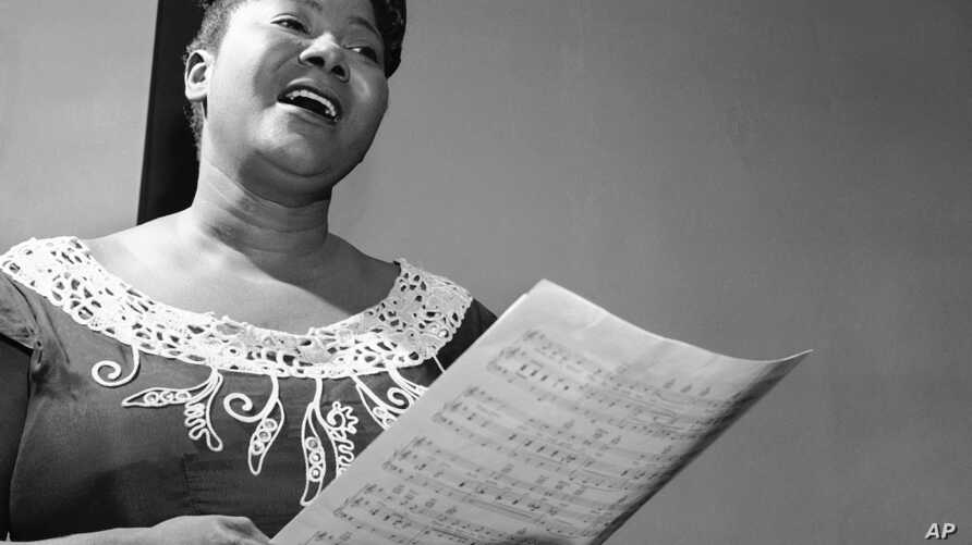 "Mahalia Jackson, ""Queen of the Gospel Singers,"" practices a new song in her Chicago apartment, August 30, 1955."