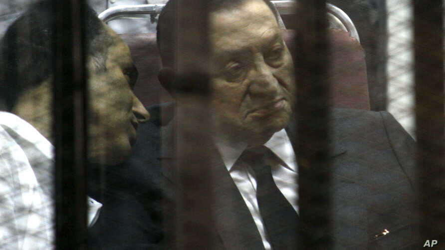 Ousted Egyptian President Hosni Mubarak, sits in the defendants cage behind protective glass, during a court hearing as he listens to his son Gamal, left, in Cairo, Egypt, Wednesday, May 21, 2014. An Egyptian court has convicted Mubarak of embezzleme