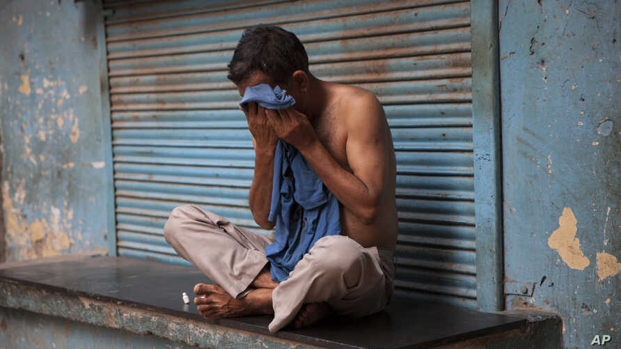 An Indian man wipes sweat off his face on a hot summer day in New Delhi, India, Sunday, May 24, 2015. Heat wave has tightened its grip over most parts of the country. More than 200 people have died since mid-April in a heat wave sweeping two southeas