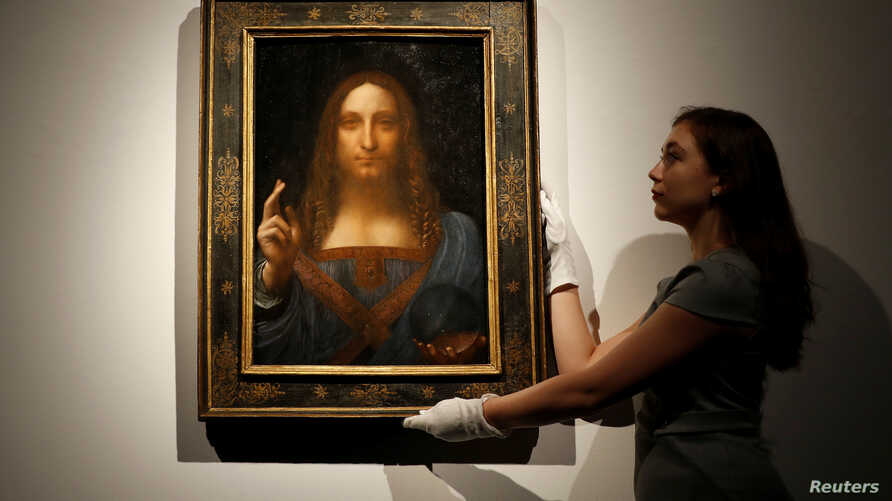 """FILE - Members of Christie's staff pose for pictures next to Leonardo da Vinci's """"Salvator Mundi"""" painting which will be auctioned by Christie's in New York in November, in London, Britain, Oct. 24, 2017."""