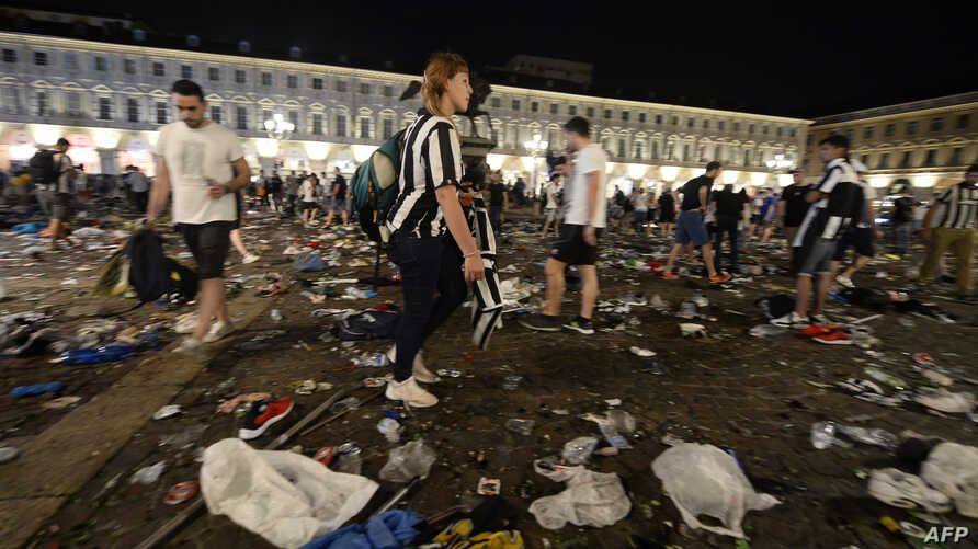 Juventus supporters look for personal belongings at Piazza San Carlo after a panic movement in the fan zone where thousands of Juventus fans were watching the UEFA Champions League Final football match between Juventus and Real Madrid on a giant scre