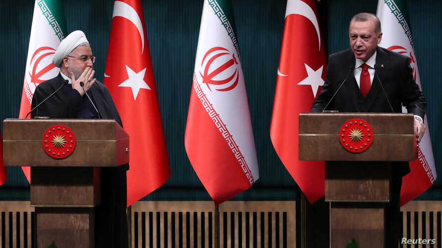 FILE - Turkish President Recep Tayyip Erdogan and his Iranian counterpart, Hassan Rouhani, hold a joint news conference after their meeting in Ankara, Dec. 20, 2018.