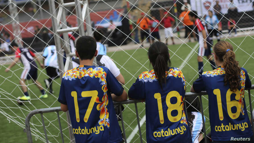 """Children from Catalonia watch a soccer match during the """"Street Soccer World Cup"""" in Sao Paulo, Brazil, July 7, 2014."""