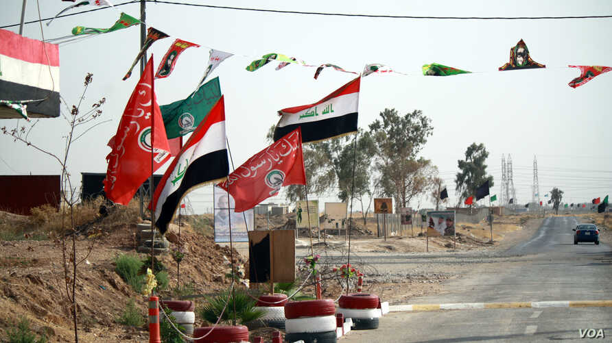 Shia and Iraqi flags adorn Hashd Shaaby bases and were hung with more frequency in the run-up to the Sept. 25 independence referendum, a show of support for Baghdad in the disputed city on Sept. 26, 2017, outside of Kirkuk city. (Photo: H. Murdock /