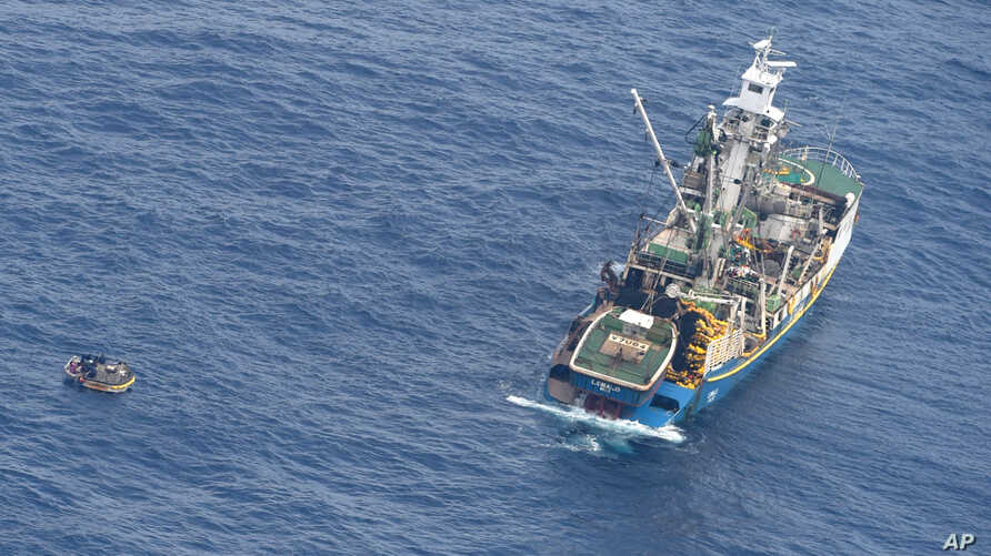 This photo released by the New Zealand Defence Force shows a wooden dinghy, left, carrying seven survivors from a missing ferry and a fishing boat in the Pacific Ocean, Jan. 28, 2018.