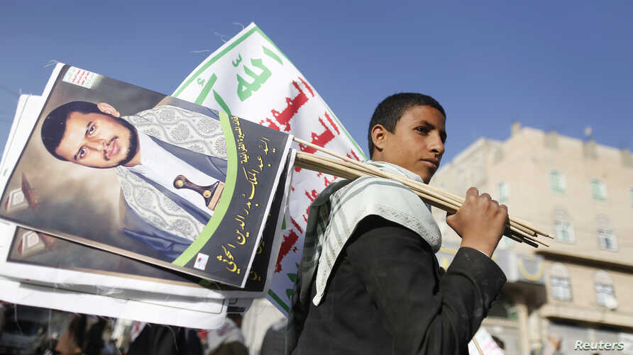 FILE - A supporter carries posters depicting Houthi leader Abdel-Malek al-Houthi during a rally in Sana'a, Yemen, March 6, 2015.
