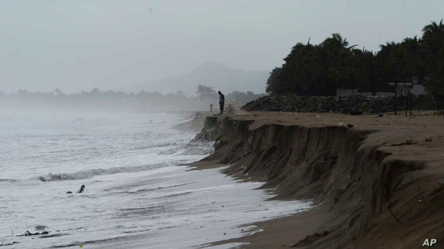 FILE - A man looks out at the Pacific ocean after heavy waves took away part of the beach in Pie de La Cuesta, on the outskirts of Acapulco, Guerrero state, Sept. 14, 2017. The weather service warned Sunday of intense storms ahead as Tropical Storm B