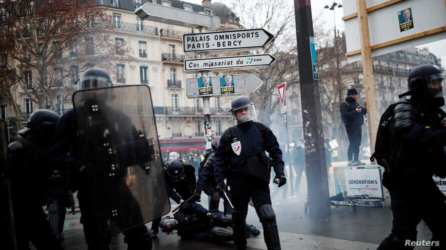 """A French policeman in riot gear, injured during clashes with protesters, is given help during a demonstration by the """"yellow vests"""" movement at Place de la Bastille in Paris, Jan. 26, 2019."""