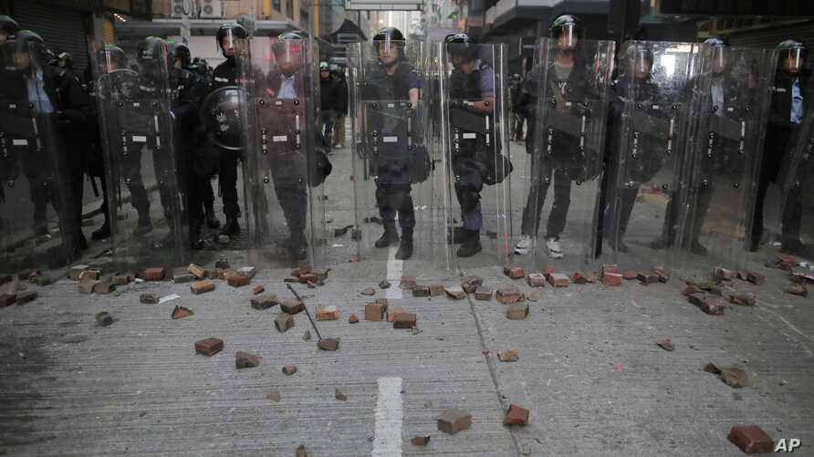 Riot police stand guard as rioters set fires and throw bricks in Mong Kok district of Hong Kong, Feb. 9, 2016.